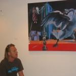 Exposant Rob Visje bij één van zijn schilderijen.
